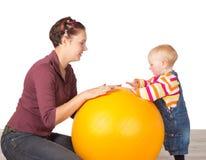 Madre y bebé con una bola de la gimnasia Fotografía de archivo