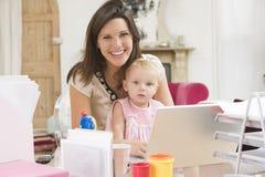 Madre y bebé en Ministerio del Interior con la computadora portátil Imagenes de archivo