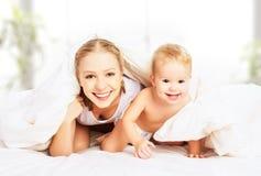 Madre y bebé felices de la familia debajo de las mantas en cama Foto de archivo libre de regalías