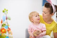 Madre y bebé que comen la galleta del conejo de Pascua Imágenes de archivo libres de regalías