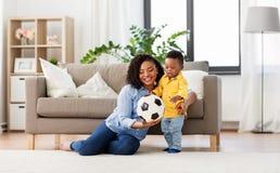 Madre y beb? que juegan con el bal?n de f?tbol en casa imágenes de archivo libres de regalías