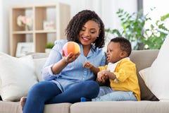 Madre y beb? que juegan con la bola en casa foto de archivo libre de regalías
