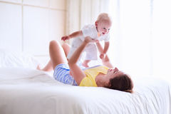 Madre y bebé que se relajan en el dormitorio blanco Fotografía de archivo