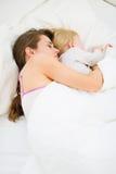 Madre y cabrito que duermen junto en cama Imagen de archivo