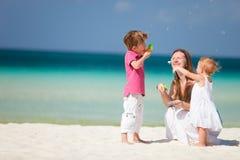 Madre y cabritos que se divierten en la playa Fotos de archivo libres de regalías
