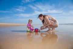Madre y cubo del bebé en la playa Imágenes de archivo libres de regalías
