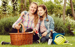 Madre y dauther jovenes con las herramientas que cultivan un huerto adentro al aire libre Imagen de archivo libre de regalías