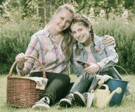 Madre y dauther jovenes con las herramientas que cultivan un huerto adentro al aire libre Foto de archivo libre de regalías