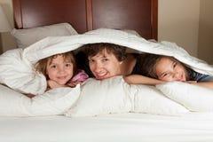 Madre y dos hijas en cama Imágenes de archivo libres de regalías