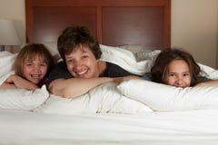 Madre y dos hijas en cama Foto de archivo libre de regalías