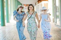 Madre y dos hijas que caminan de com?n acuerdo en la columnata fotos de archivo