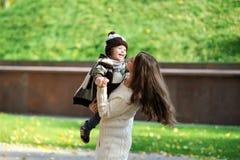 Madre y el paseo del niño en parque Fotos de archivo