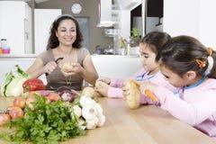 Madre y gemelos que pelan las patatas en cocina Fotografía de archivo libre de regalías