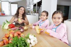 Madre y gemelos que pelan las patatas en cocina Foto de archivo libre de regalías