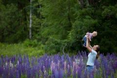 Madre y hija en el campo de las flores del Lupine Foto de archivo libre de regalías