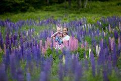 Madre y hija en el campo de las flores del Lupine Imagen de archivo libre de regalías
