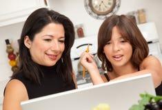 Madre y hija hispánicas atractivas que usa la computadora portátil Imágenes de archivo libres de regalías