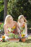 Madre y hija que cultivan un huerto plantando las flores Imágenes de archivo libres de regalías