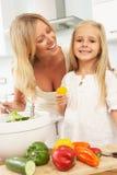 Madre y hija que preparan la ensalada en cocina Foto de archivo