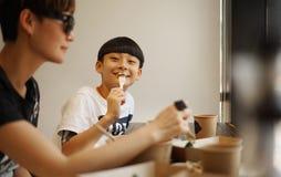Madre y hijo asiáticos que comen el almuerzo en un restaurante Fotografía de archivo