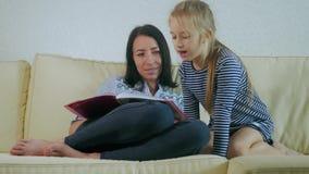 Madre y libro de lectura joven de la hija en el sofá en casa Mida el tiempo solamente para la madre y su pequeña hija almacen de metraje de vídeo