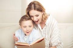 Madre y libro del abarcamiento y de lectura del hijo que se sienta junto Fotografía de archivo