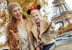 Madre y muchacha en los oídos de Minnie Mouse que muestran los pulgares para arriba, París Fotos de archivo