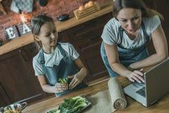Madre y muchacha que usa el ordenador portátil en cocina Imagen de archivo