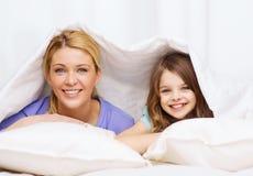 Madre y niña debajo de la manta en casa Imagen de archivo libre de regalías