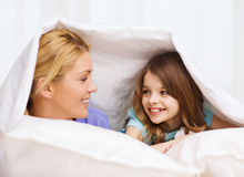 Madre y niña debajo de la manta en casa Imagen de archivo