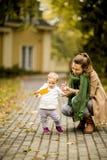 Madre y niña en el parque del otoño foto de archivo