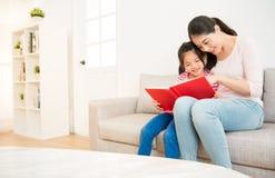 Madre y niña que leen un libro imagenes de archivo