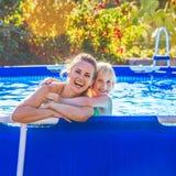 Madre y niño activos felices en el abarcamiento de la piscina Imagen de archivo