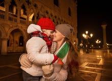 Madre y niño con la bandera italiana en la plaza San Marco en Venecia Fotos de archivo libres de regalías