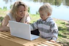 Madre y niño con la computadora portátil imagen de archivo libre de regalías