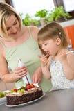 Madre y niño con la torta de chocolate en cocina Fotos de archivo