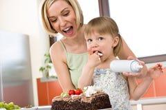 Madre y niño con la torta de chocolate en cocina Foto de archivo libre de regalías