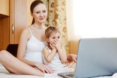 Madre y niño embarazados felices con el comput de la computadora portátil Imagen de archivo libre de regalías