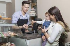 Madre y niño en el escritorio de efectivo de una tienda de los pasteles Imagen de archivo