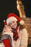Madre y niño en sombreros de la Navidad cerca de Palazzo Vecchio, Italia Imagenes de archivo