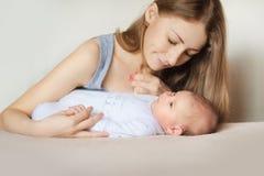 Madre y niño en una cama blanca fotografía de archivo