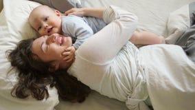 Madre y niño en una cama blanca Mamá y bebé en el pañal que juega en dormitorio soleado Padre y niño que se relajan en metrajes