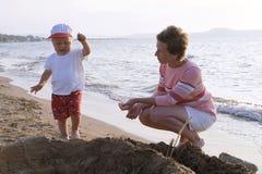 Madre y niño en una playa Foto de archivo libre de regalías