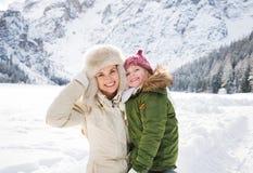 Madre y niño felices al aire libre delante de las montañas nevosas Fotos de archivo
