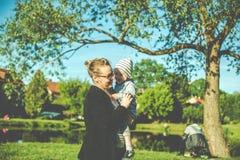 madre y niño felices en parque imagenes de archivo