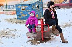 Madre y niño jovenes cansados en un oscilación en invierno Fotos de archivo