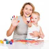 Madre y niño jovenes felices con las manos pintadas Foto de archivo libre de regalías