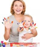 Madre y niño jovenes felices con las manos pintadas Foto de archivo