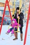 Madre y niño jovenes felices en un oscilación, invierno frío Fotografía de archivo