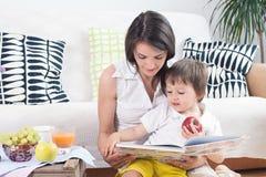 Madre y niño, leyendo un libro y comiendo las frutas Imagen de archivo libre de regalías